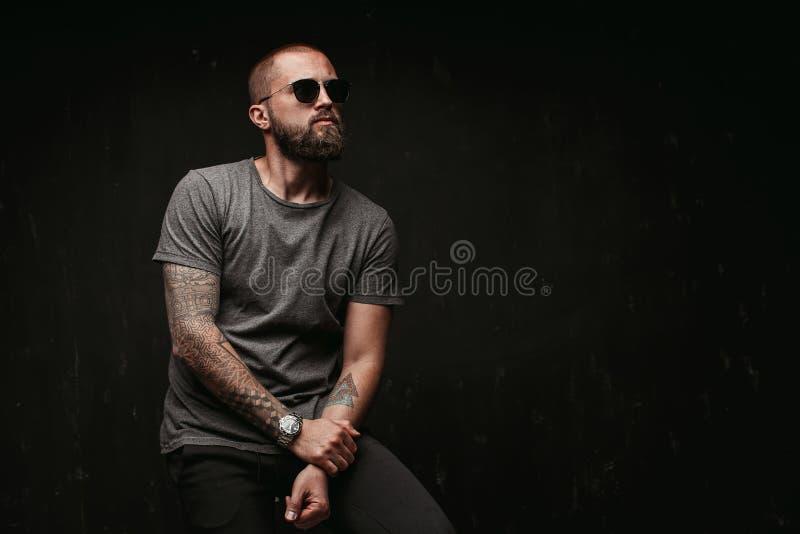 Stående av en stilig bliven skallig man med lång väl klippt bärande solglasögon för skägg och gråa skjortan som bort ser för att  royaltyfria bilder