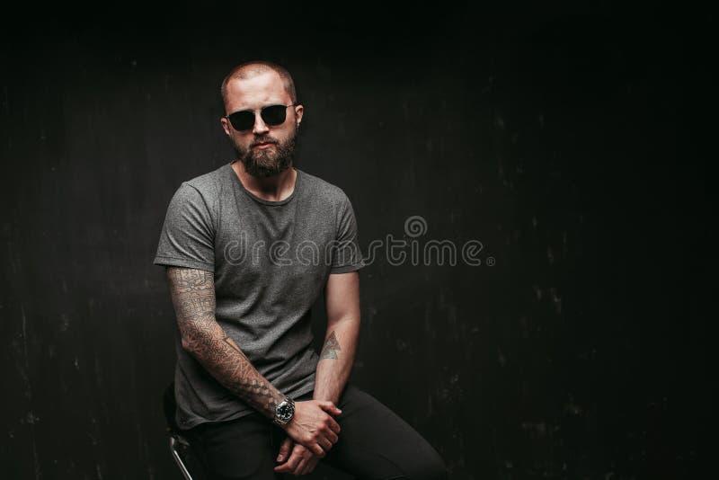 Stående av en stilig bliven skallig man med lång väl klippt bärande solglasögon för skägg och gråa skjortan som ser kameran arkivbild