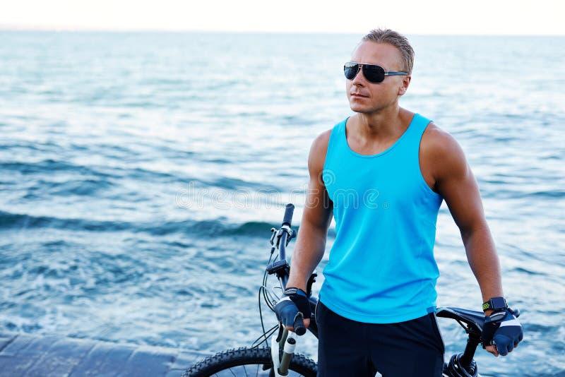 Stående av en stilig blond idrotts- man med cykeln utomhus på stranden royaltyfria bilder