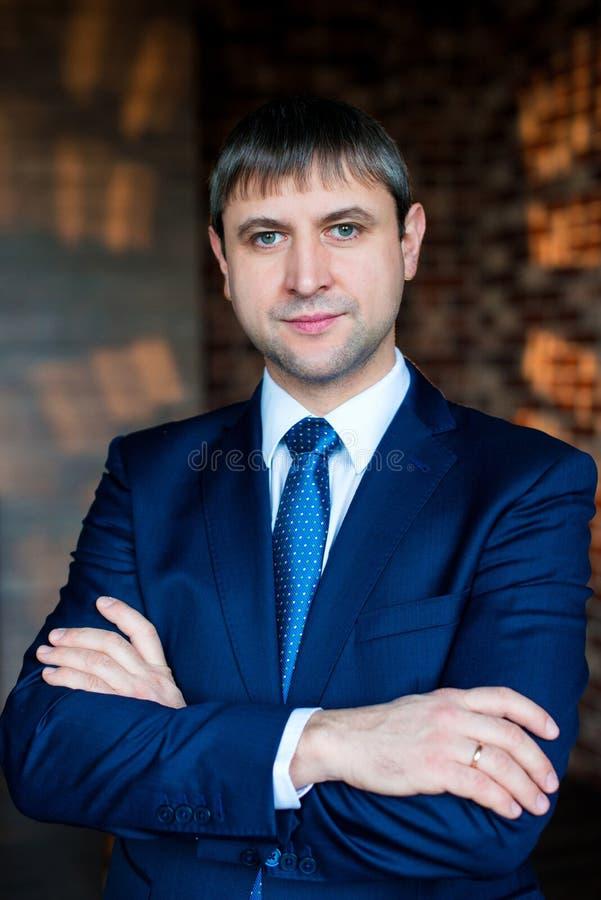 Stående av en stilig man i en affärsdräkt i en vindinre arms affärsmannen korsad standing arkivfoto