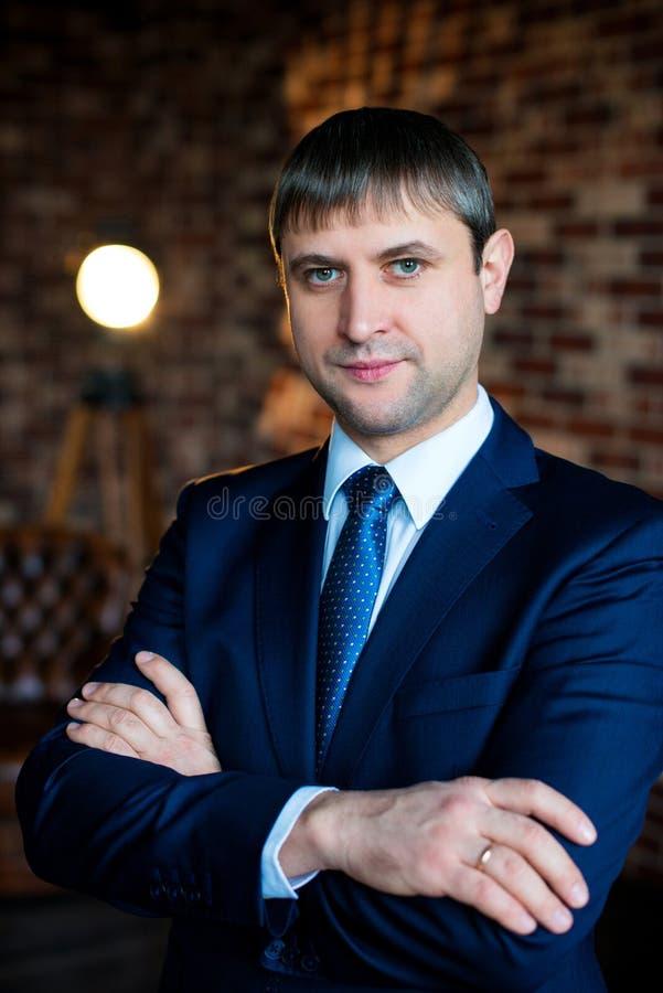 Stående av en stilig man i en affärsdräkt i en vindinre arms affärsmannen korsad standing arkivfoton