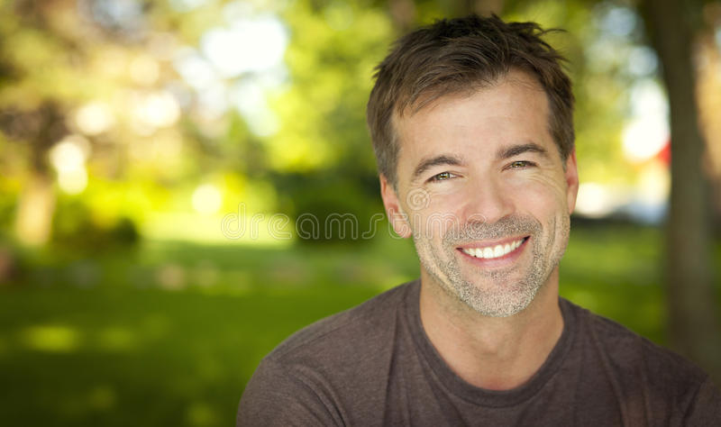 Stående av en stilig man som ler på kameran royaltyfria bilder