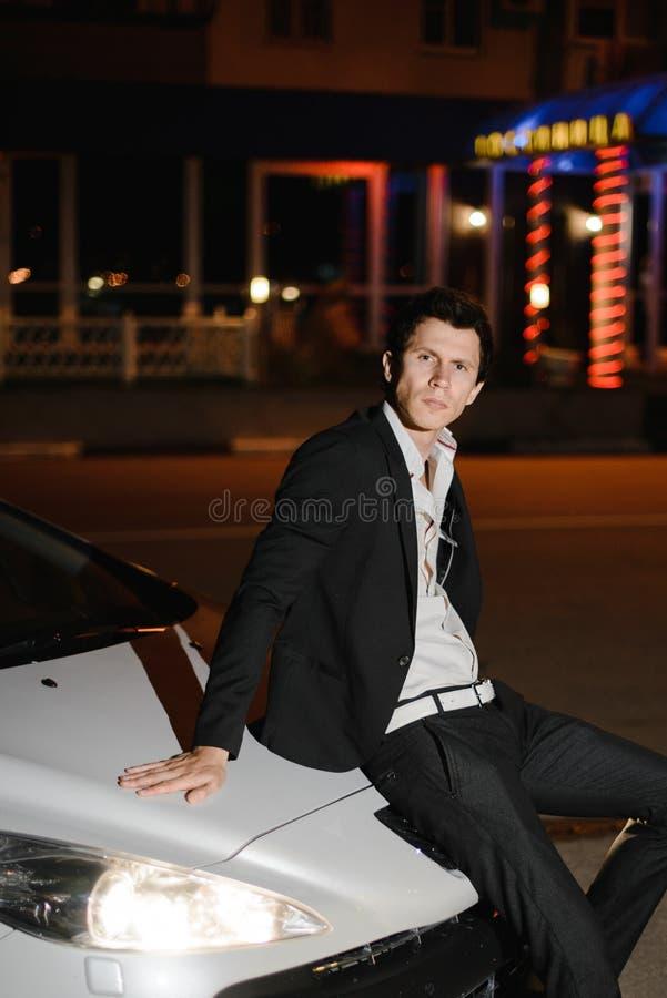 Stående av en stilig man som sitter på bilhuven av hans vita cabriolet uteliv Affärsman i dräkt i lyxig bil arkivfoton