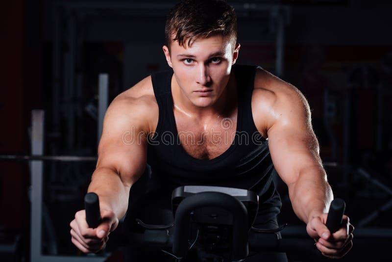 Stående av en stilig mangenomkörare på kondition motionscykelmörkret på idrottshallen arkivfoton