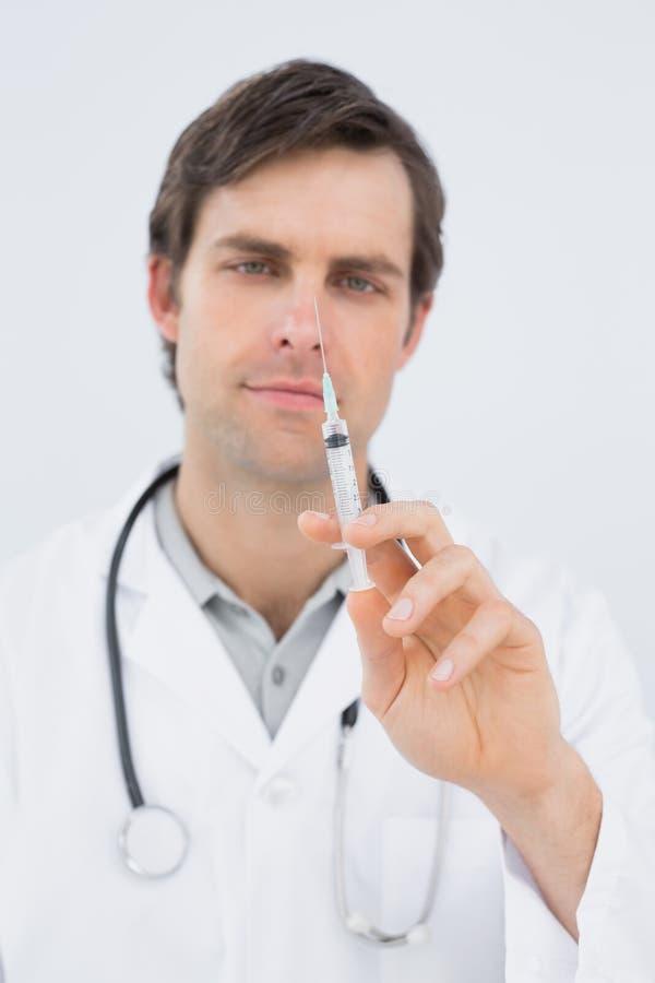 Stående av en stilig manlig doktor som rymmer en injektion arkivbilder