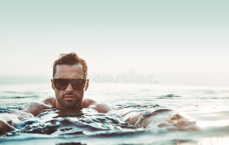 Stående av en stilig muskulös man som kopplar av i ett varmt tropiskt vatten fotografering för bildbyråer