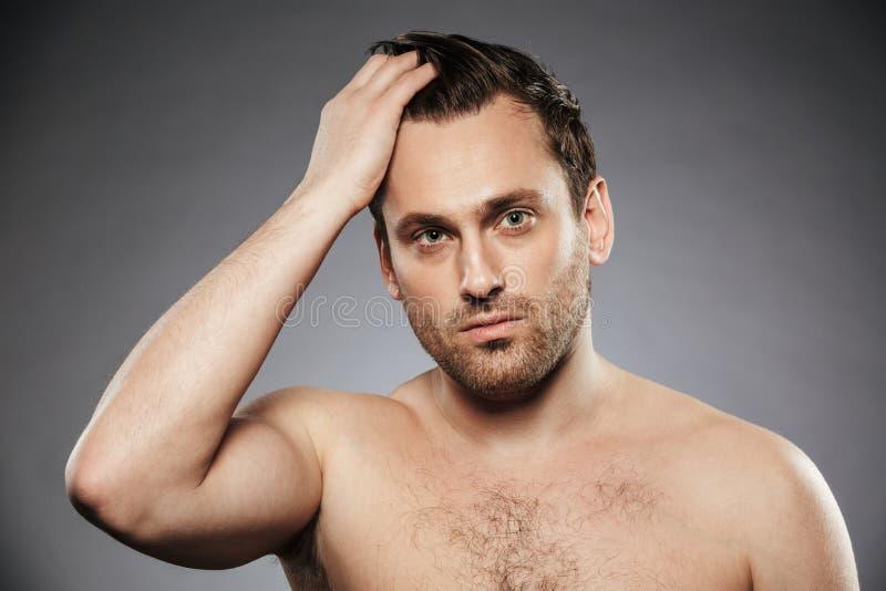 Stående av en stilig shirtless man som fixar hans hår arkivfoton