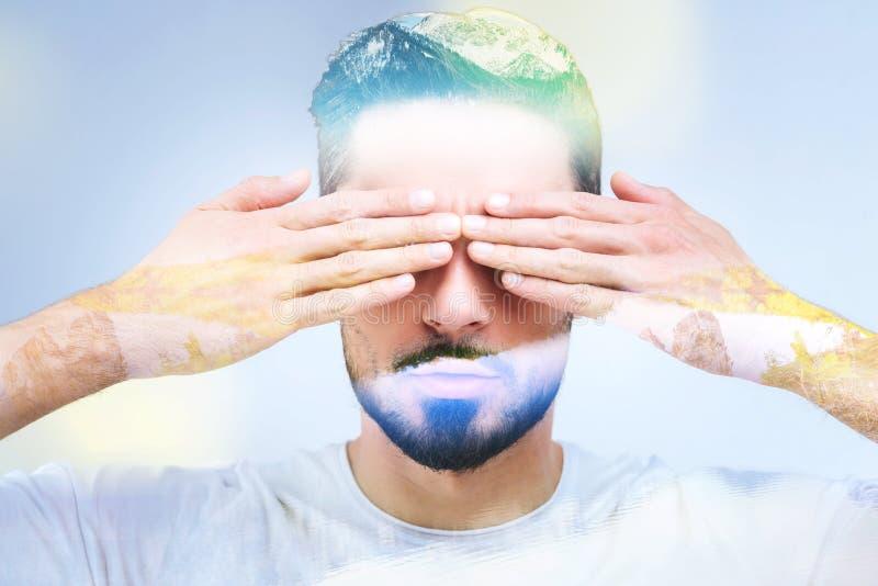 Stående av en stilig skäggig man som täcker hans ögon arkivfoton