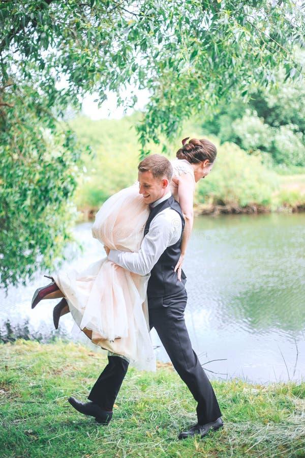 Stående av en stilig ung man som utomhus bär den attraktiva kvinnan på hans tillbaka Roliga par Brud och gr arkivbilder