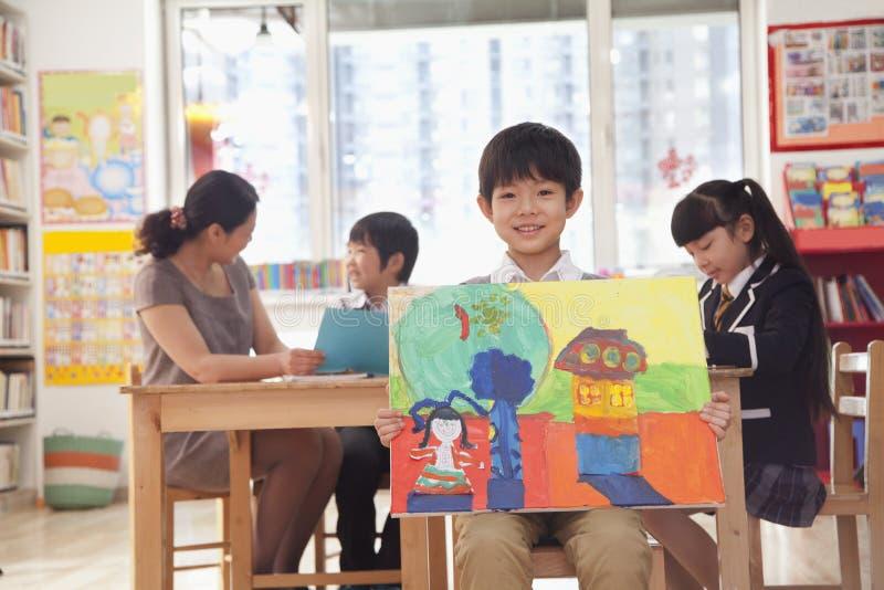 Stående av en student som rymmer en målning royaltyfri fotografi