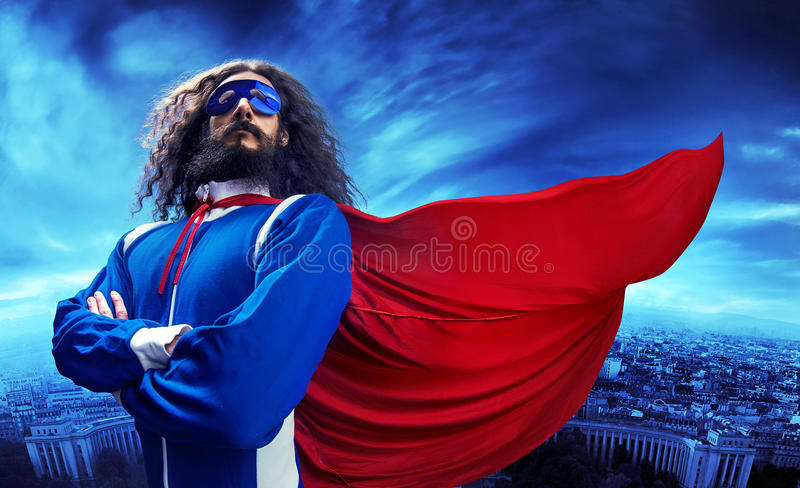 Stående av en superheroe som poserar över det stads- landskapet royaltyfria bilder