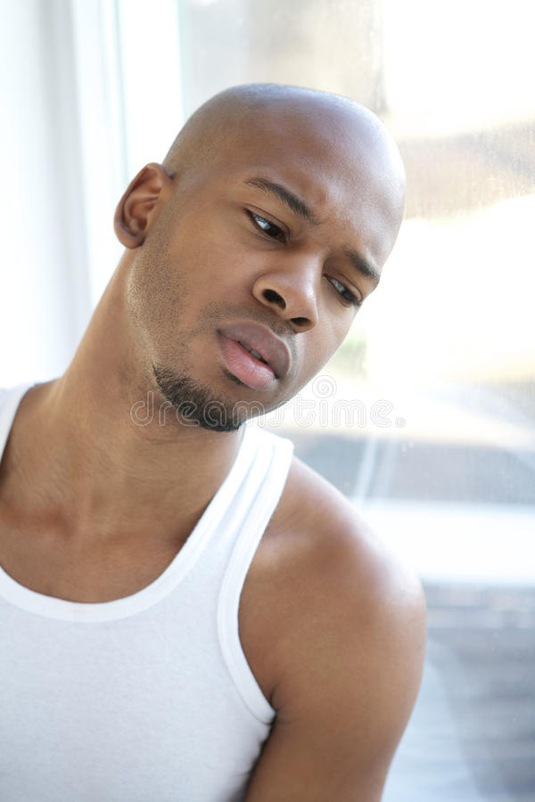 Stående av en svart man som ser ut ur fönster arkivbild