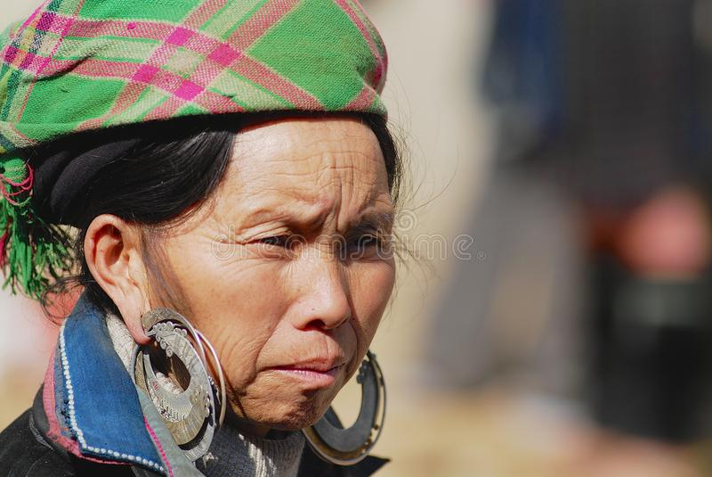 Stående av en svart Miao Hmong minoritetkvinna som bär den traditionella dräkten på gatan i Sapa, Vietnam royaltyfri foto