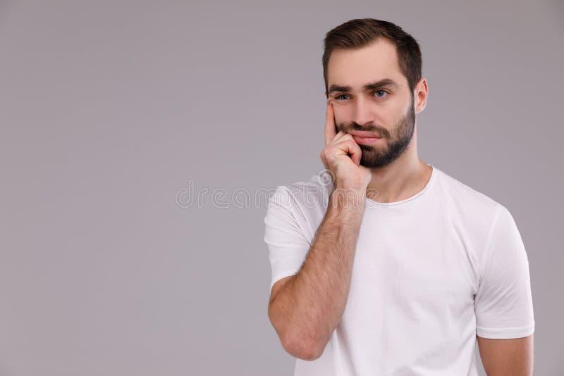 Stående av en tänkande man i en vit T-tröja på en grå bakgrund royaltyfri foto