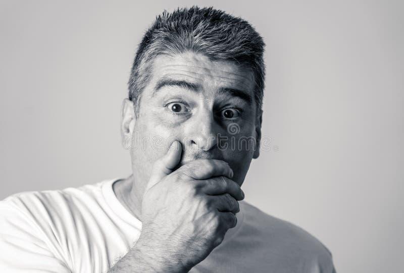 Stående av en 40-tal50-talman i chock med ett förskräckt uttryck på hans framsida som gör skrämda gester i mänskliga sinnesrörels fotografering för bildbyråer