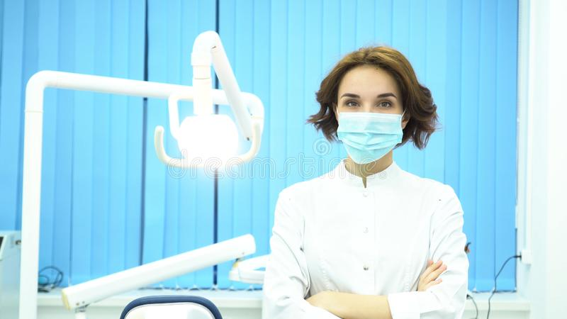 Stående av en tandläkare som sätter på maskeringen som ser kameran på den tand- kliniken Stående armar för kvinnlig tandläkareass royaltyfria foton