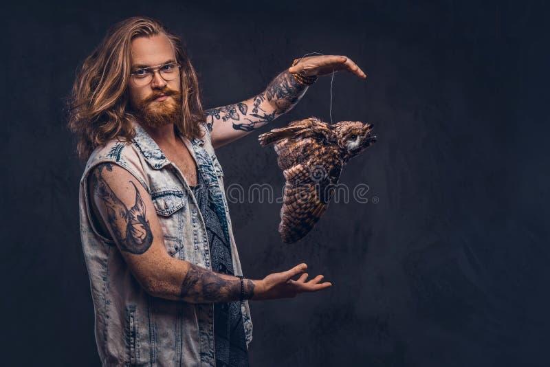 Stående av en tattoed rödhårig manhipsterman med långt det iklädda frodigt hår och fulla skägget enskjorta och omslagshåll royaltyfri foto