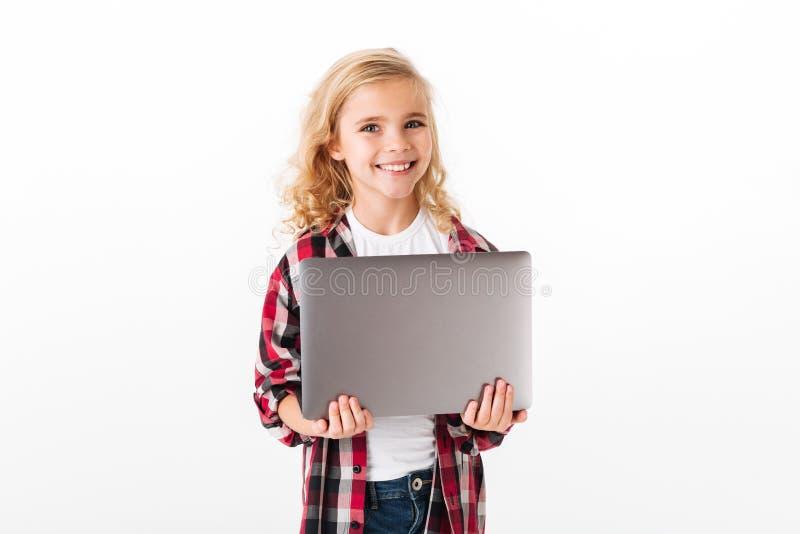 Stående av en tillfredsställd hållande bärbar datordator för liten flicka arkivfoto
