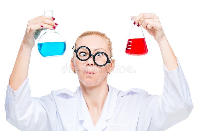 stående av en tokig labbtekniker med två flaskor av kulöra prenumerationer royaltyfri fotografi