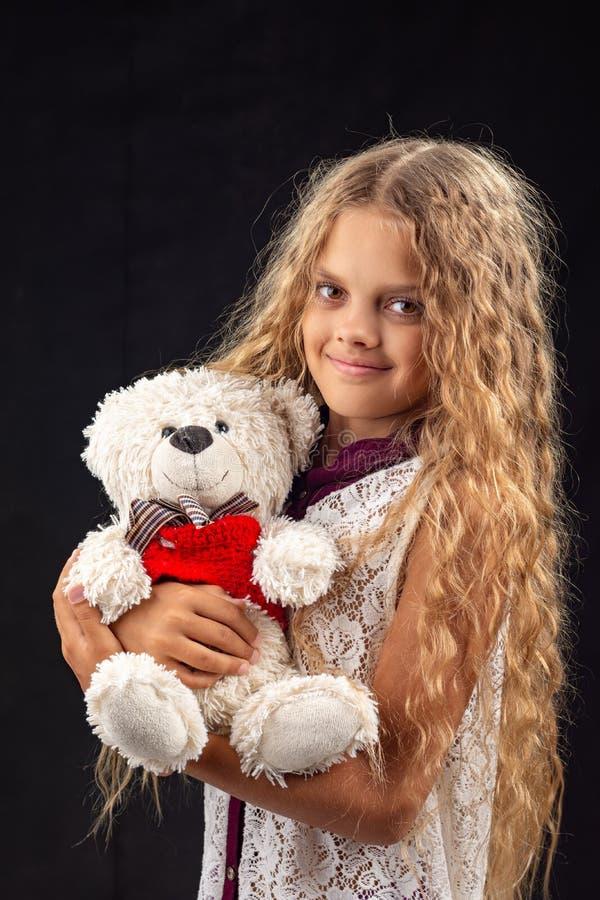 Stående av en tonårs- flicka med en gammal leksakbjörn arkivbilder