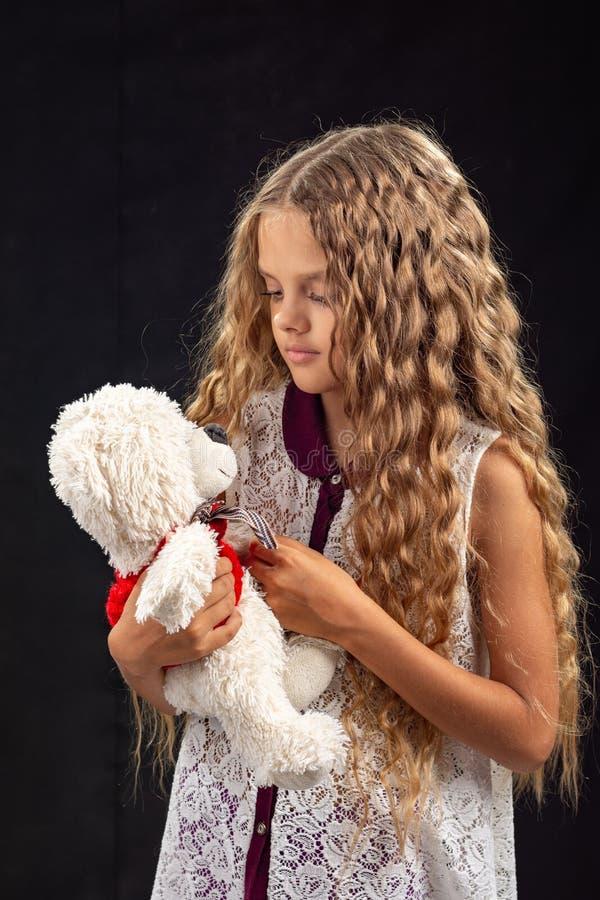 Stående av en tonårs- flicka med en gammal nallebjörn, en favorit- barndomleksak royaltyfri foto