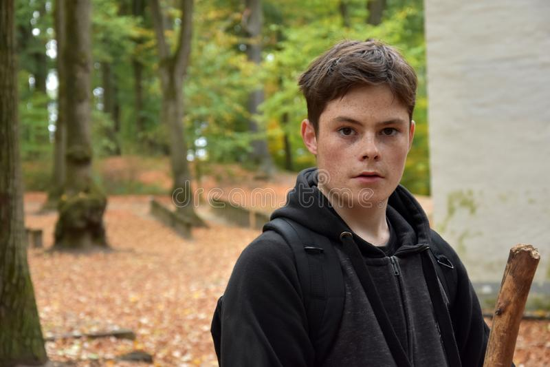 Stående av en tonårs- pojke i höstskog royaltyfria foton