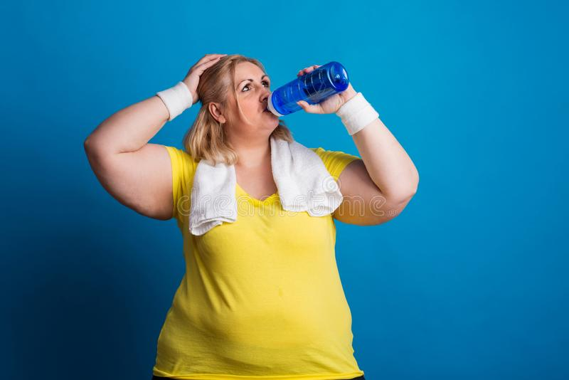 Stående av en trött överviktig kvinna i studion på en blå bakgrund, dricksvatten royaltyfri foto