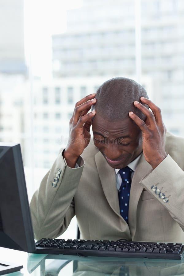Stående av en trött kontorsarbetare som använder en dator royaltyfria foton
