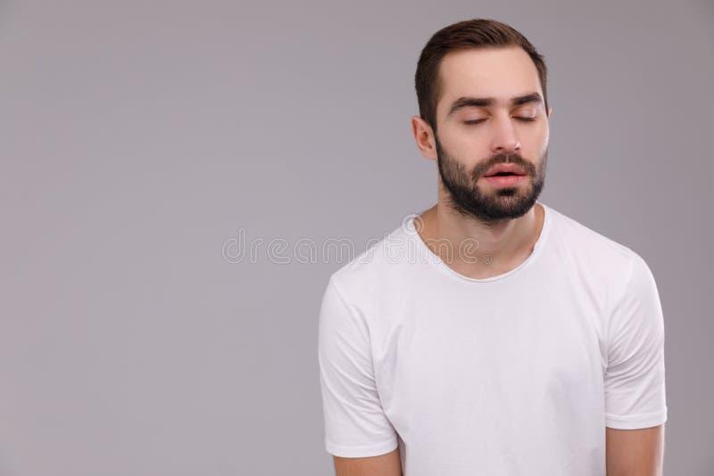 Stående av en trött man i en vit T-tröja på en grå bakgrund royaltyfri fotografi