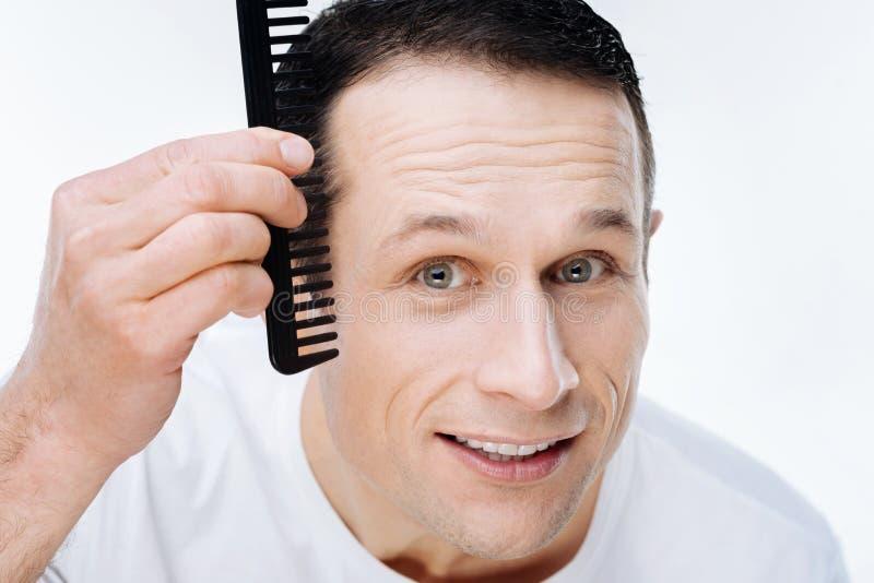 Stående av en trevlig positiv man som använder en hårkam royaltyfri foto