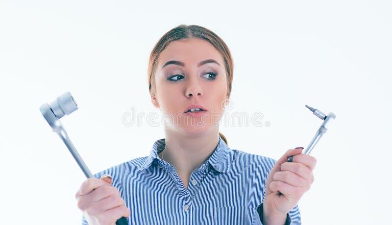Stående av en tvivelaktigt flicka med ett hjälpmedel som inte vet vad för att göra med dem, isolerat på vit arkivbilder