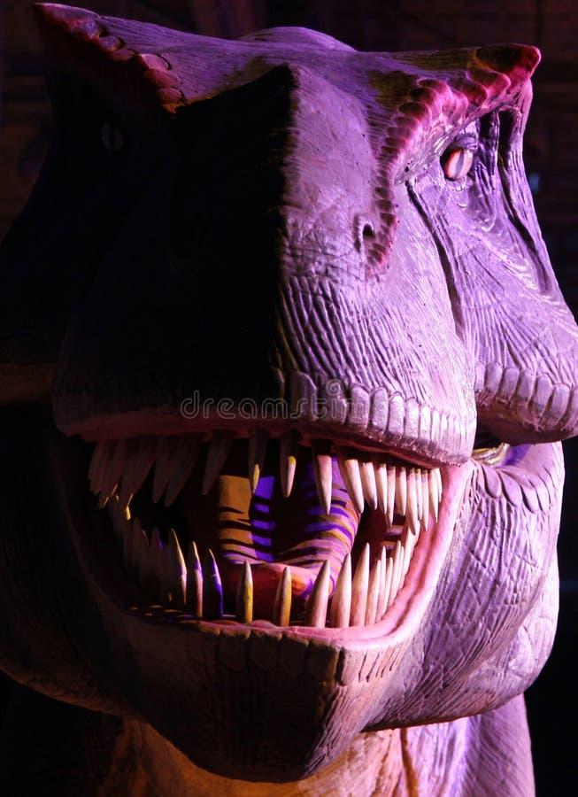 Stående av en tyrannosarie i mörkret på utställningstaden av dinosaurier arkivfoto