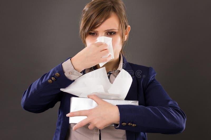 Stående av en ung affärskvinna med influensa som blåser hennes näsa arkivbilder