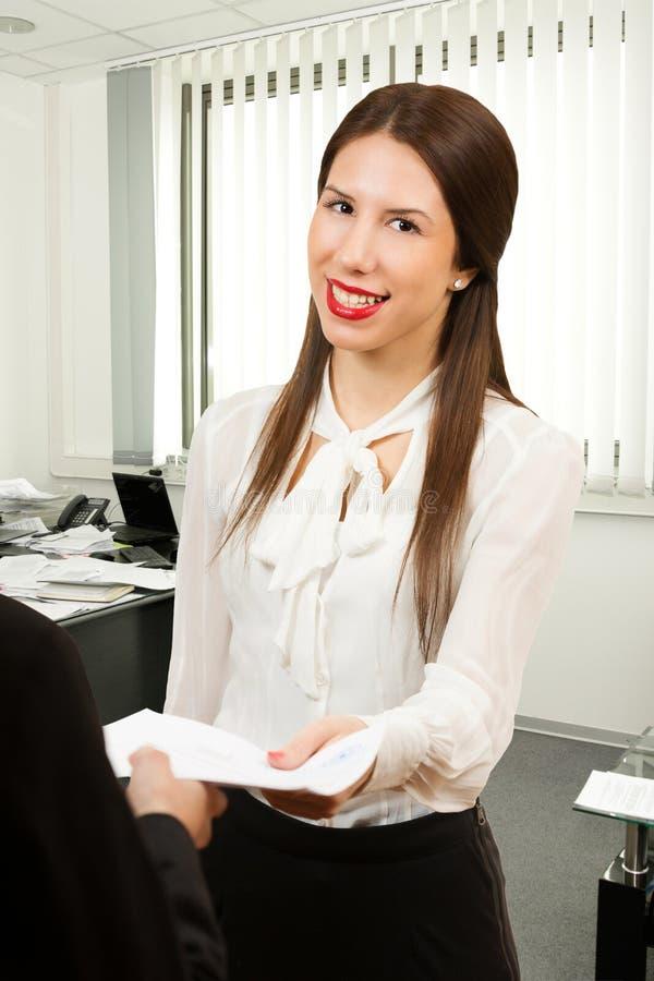 Stående av en ung affärskvinna som rymmer avtalet arkivbilder