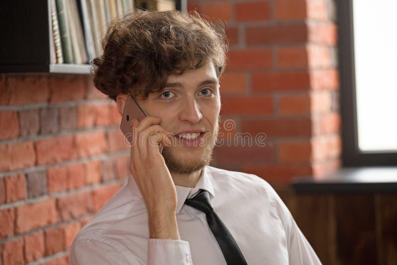 Stående av en ung affärsman som talar på mobiltelefonen arkivfoton