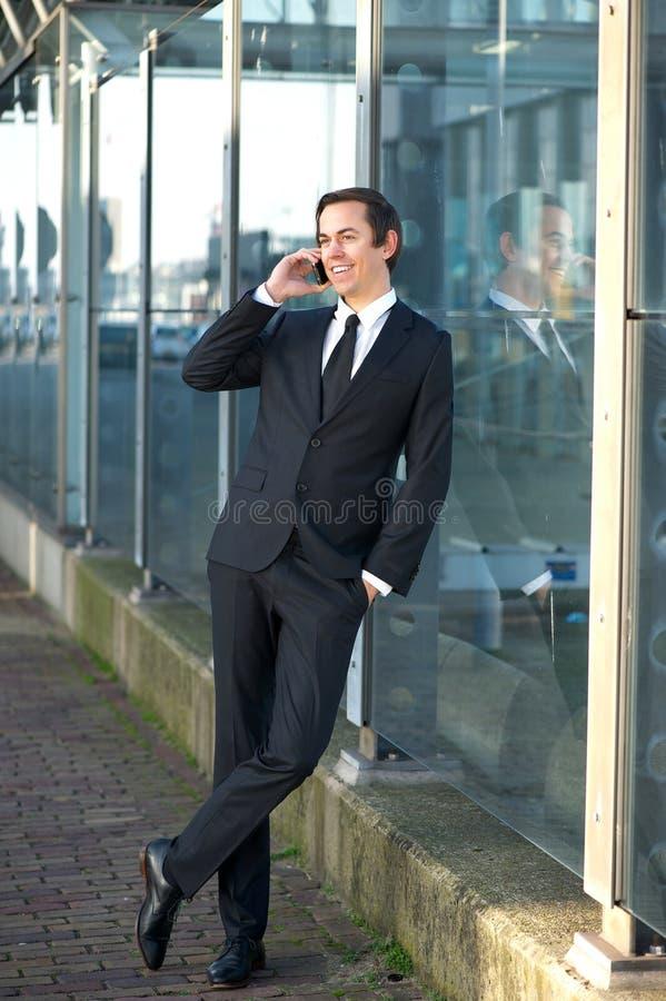 Stående av en ung affärsman som utomhus talar på mobiltelefonen arkivfoto
