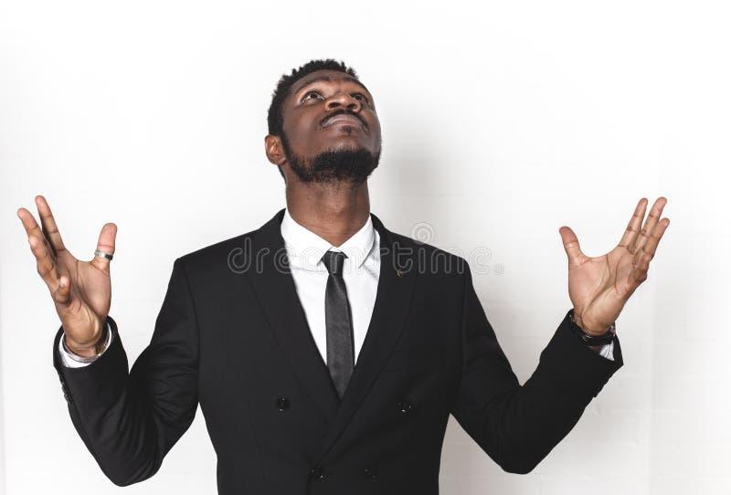 Stående av en ung afrikansk amerikan i en affärsdräkt Sinnesrörelser på framsidan mannen kastar upp hans händer och blickar till royaltyfri bild