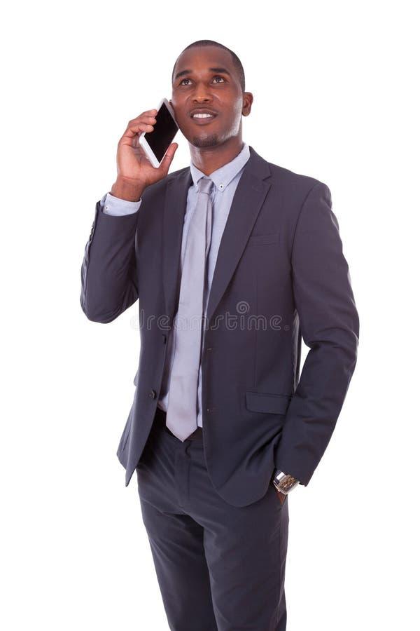 Stående av en ung afrikansk amerikanaffärsman som gör en mobil arkivbilder
