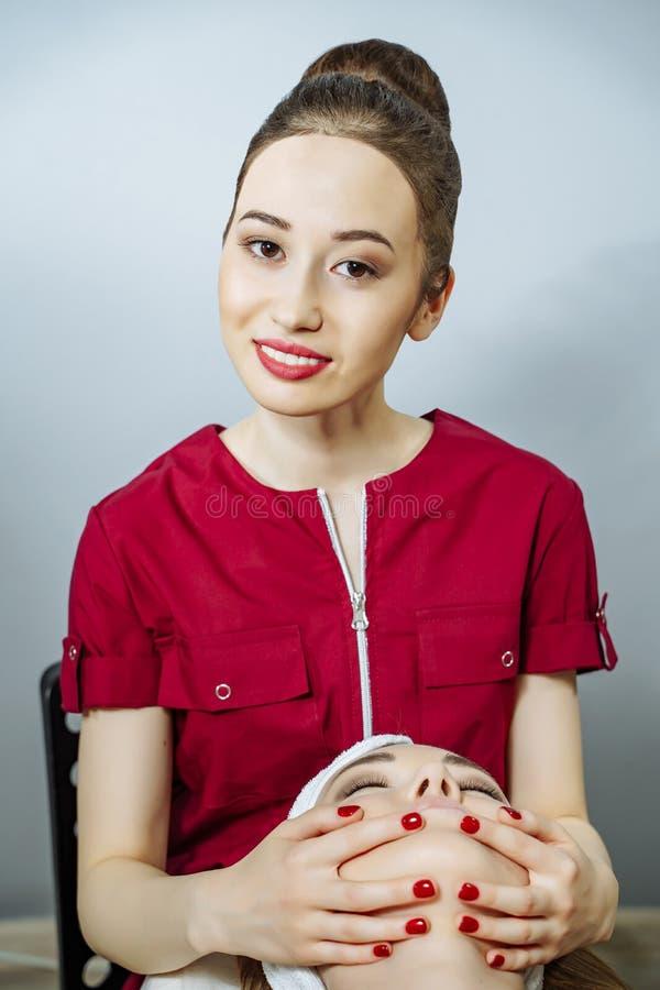 Stående av en ung asiatisk kvinnakosmetolog som gör ansikts- massage till en flicka royaltyfri bild