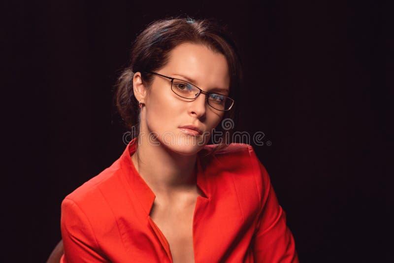 Stående av en ung attracrtive kvinna som sitter i rött omslag på en stol i en studio royaltyfri foto