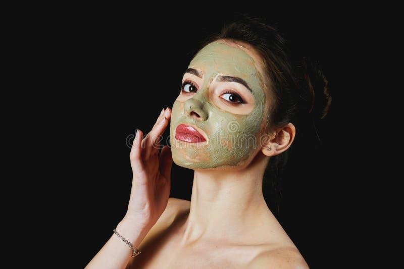 Stående av en ung attraktiv kvinna i en kosmetisk maskering arkivfoto