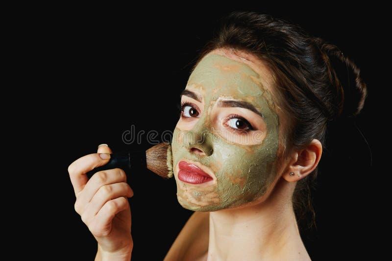 Stående av en ung attraktiv kvinna i en kosmetisk maskering arkivbild