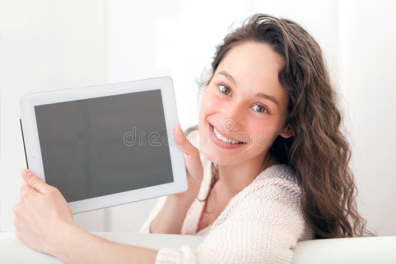 Stående av en ung attraktiv kvinna som använder minnestavlan på soffan royaltyfria bilder