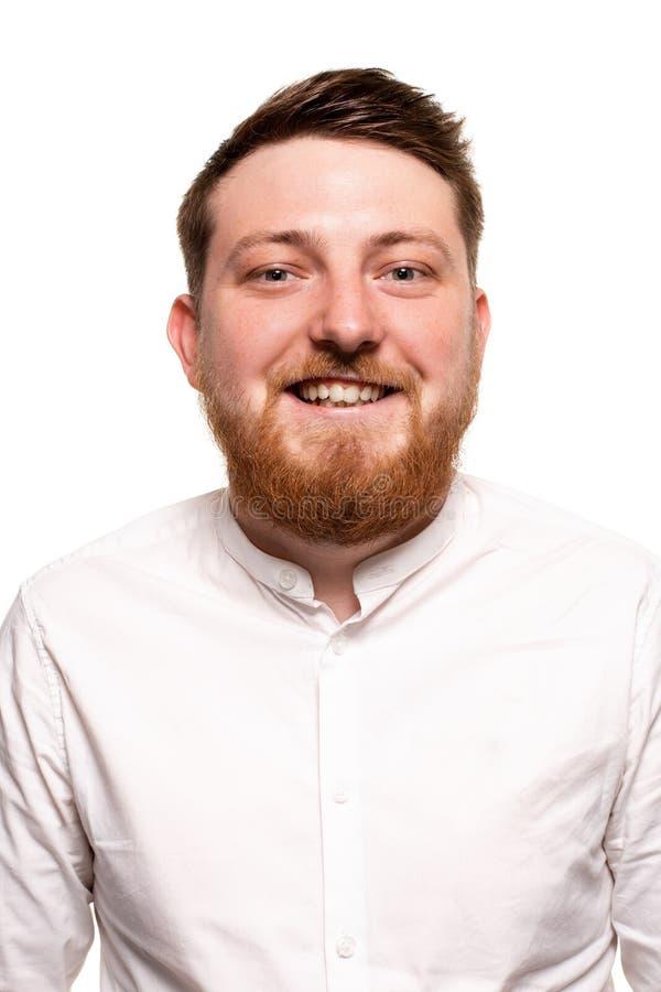 Stående av en ung attraktiv man i en vit skjorta, med skägget och mustaschen som isoleras på en vit bakgrund royaltyfri foto
