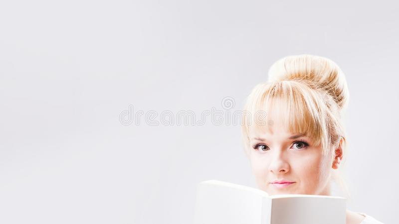 Stående av en ung blond kvinna med bullefrisyren som rymmer den vita tomma boken på ljust - grå bakgrund royaltyfri fotografi