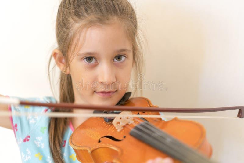 Stående av en ung blond tonårs- flicka som spelar fiolen Flicka som spelar fiolen på en ljus bakgrund arkivbild