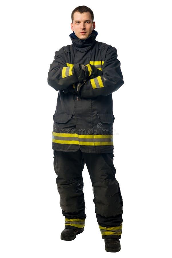 Stående av en ung brandman i isolerad kläder för smutsigt arbete royaltyfria bilder