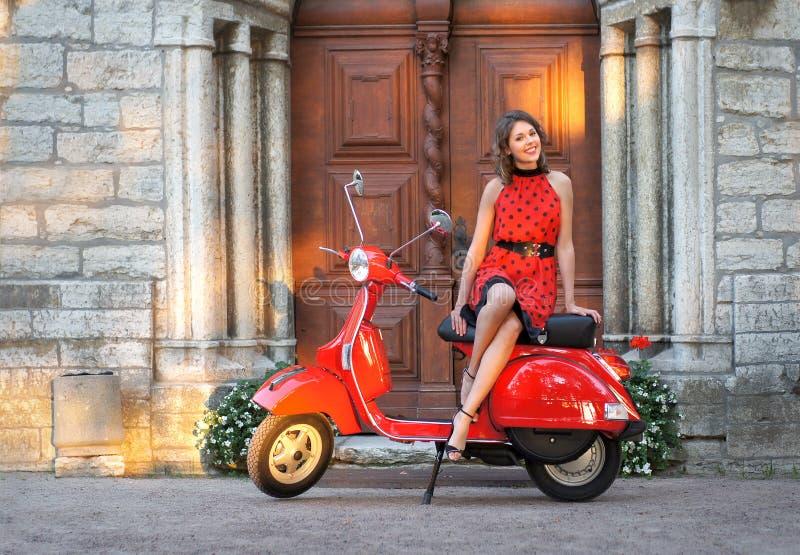 Stående av en ung brunett på en gammal röd sparkcykel royaltyfri fotografi