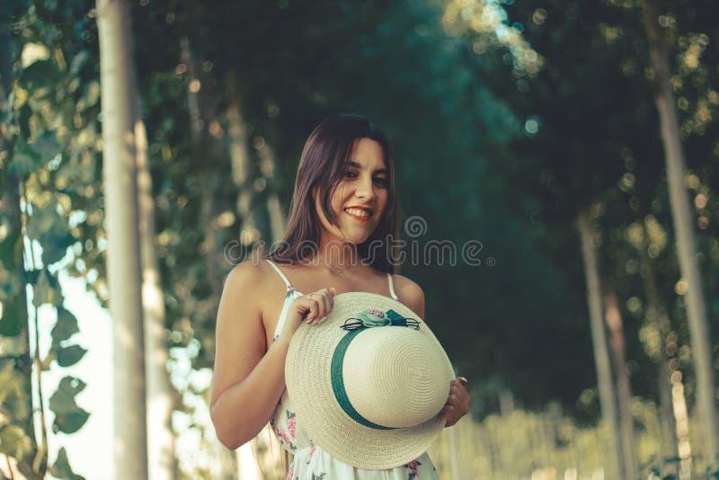 Stående av en ung brunettflicka som rymmer hennes hatt och ler på kameran fotografering för bildbyråer