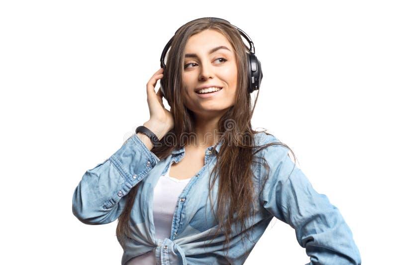Stående av en ung brunettkvinna som lyssnar till musiken med hörlurar mot vit bakgrund som isoleras arkivfoto